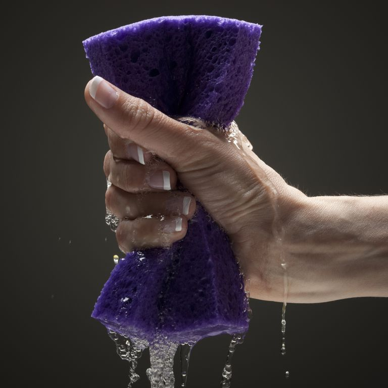 Young woman's hand squeezing wet sponge