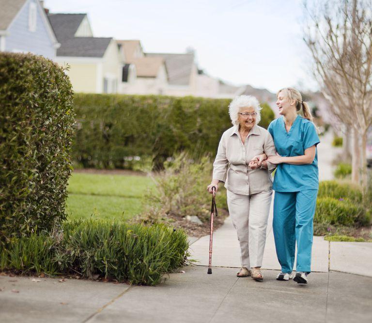 Home health aide helping elderly woman on a walk