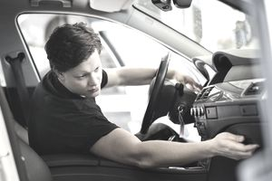 Young male auto mechanic analyzing dashboard in car