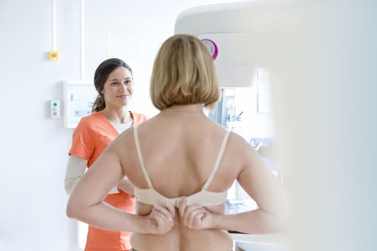 Nurse helping patient prepare for mammogram in examination room