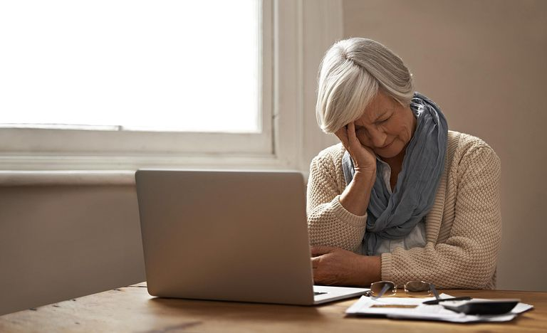 Upset woman at desk with computer, working on closing an estate.
