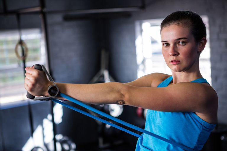 Portrait of female athlete stretching resistance band