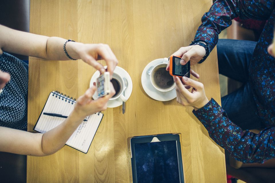 Teenagers using cellphones over coffee