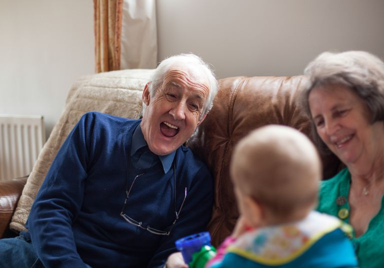 Elderly man interacting with a baby
