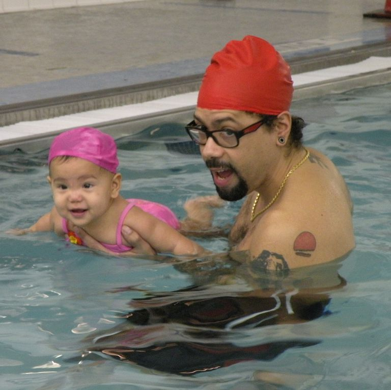 An infant taking a swimming class with her father at the YMCA.