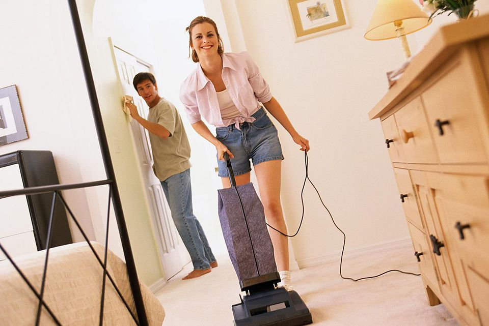 Smiling woman vacuuming, man dusting