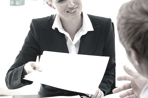 Young businesswoman giving paperwork to colleague in office