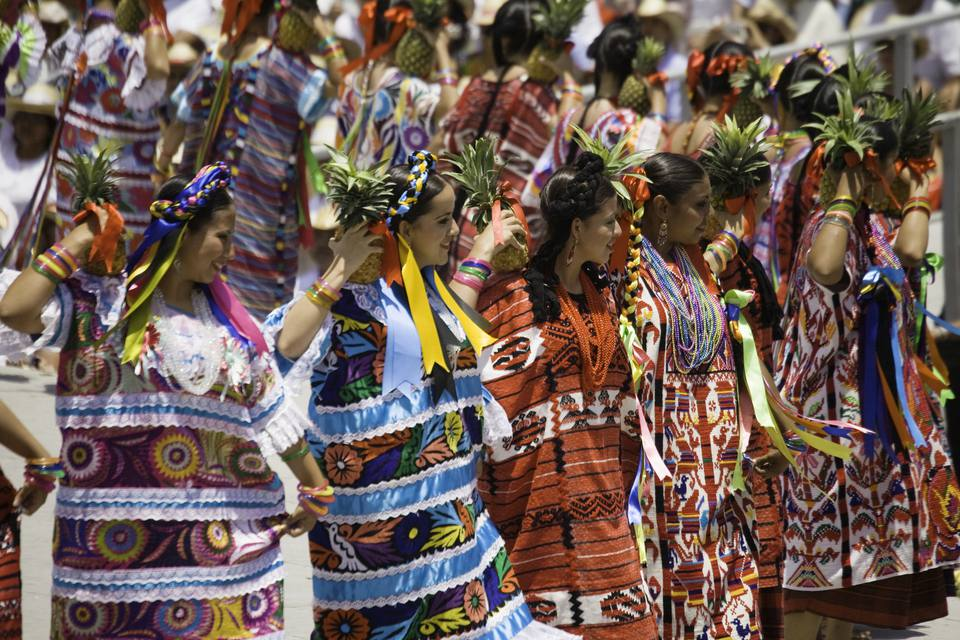Women holding pineapple and dancing in row during Flor de Pina (Pineaple dance), smiling