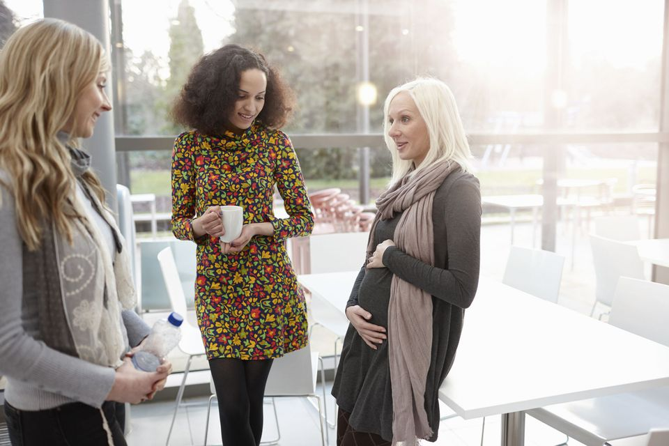 A picture of a pregnant woman talking to her co-workers