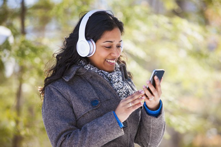 Young woman of South Asian ethnicity using cell phone and Bluetooth headphones in Scanlon Creek Conservation Area