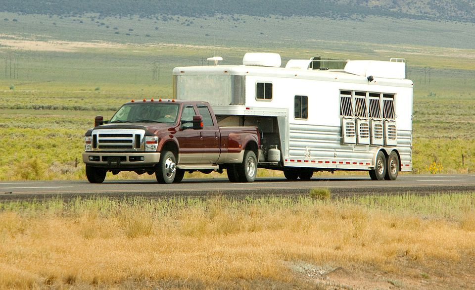 A truck pulling a goose neck horse trailer with living quarters.