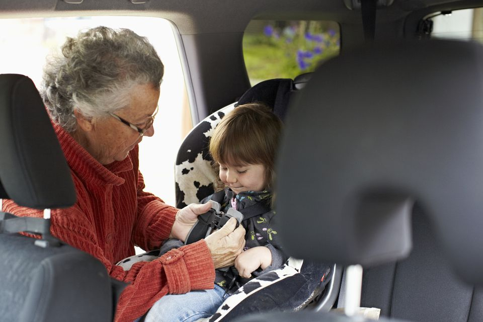 Grandmother putting grandchild in carseat