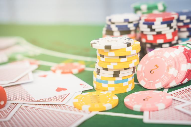 Close-Up Of Gambling Chips With Cards On Table