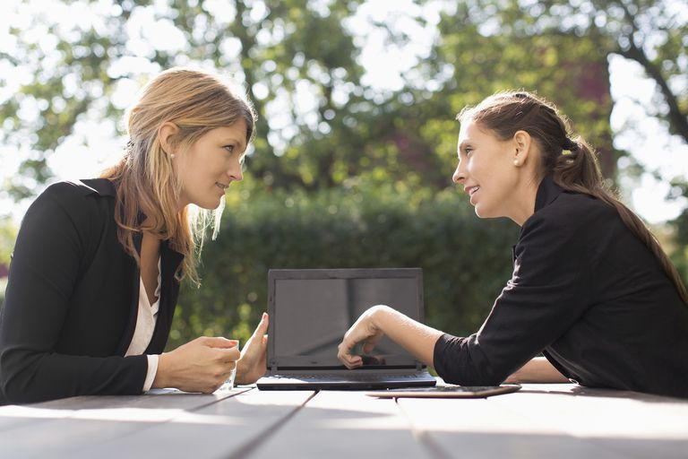 Businesswoman discussing with female colleague through laptop at outdoor cafe