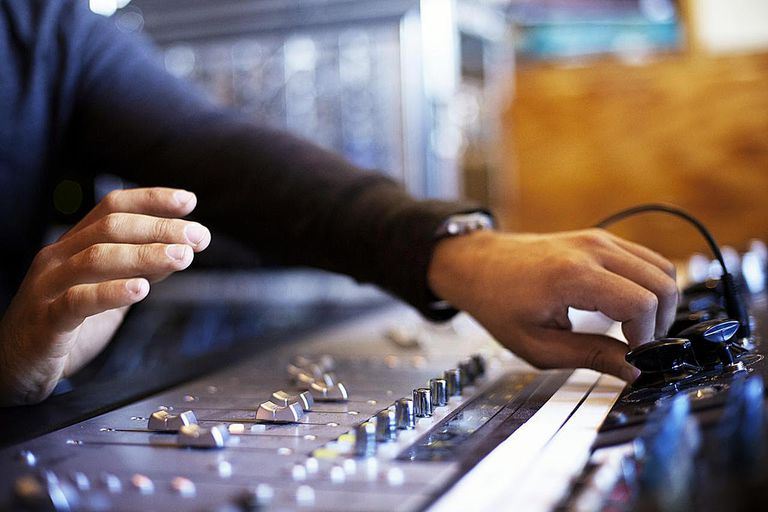 Man using audio mixing board