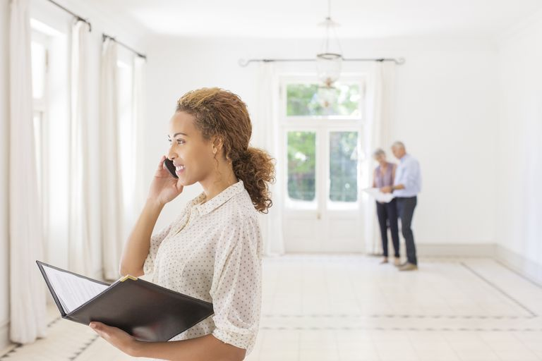 real estate agent on phone with couple in background looking at house