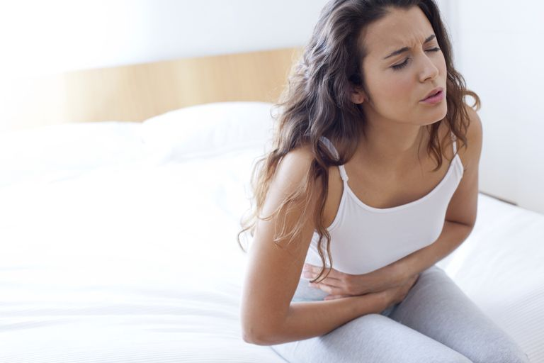 Woman on bed with cramps