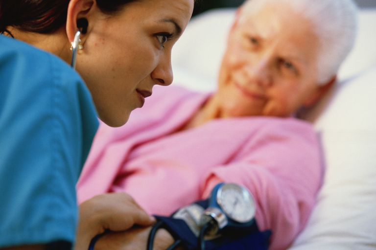 Nurse with stethoscope taking elderly patient's blood pressure