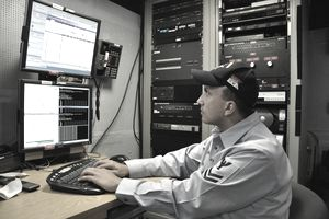 U.S. Navy Information Systems Technician 2nd Class James Rago troubleshoots the video teleconference system of a video information exchange system