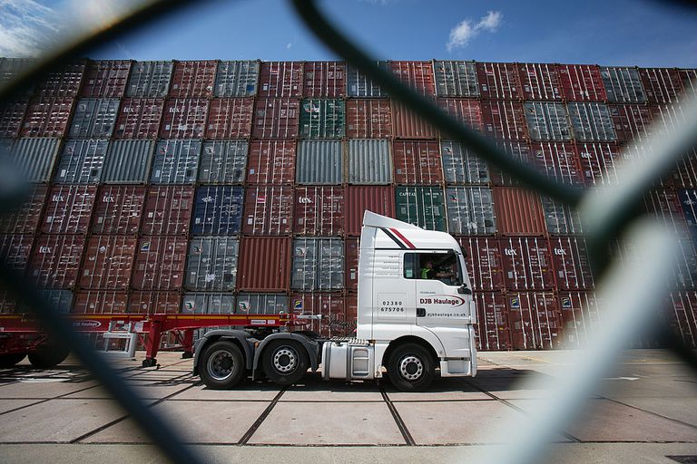 A truck passes shipping containers