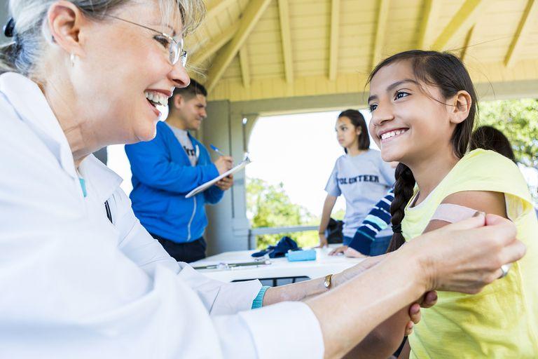 Doctor giving young girl flu shot