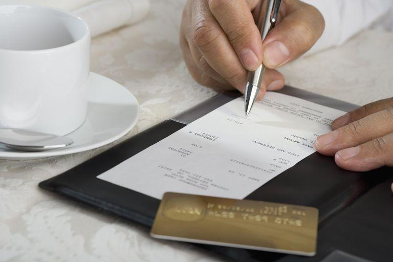 Close up of man signing credit card receipt at restaurant