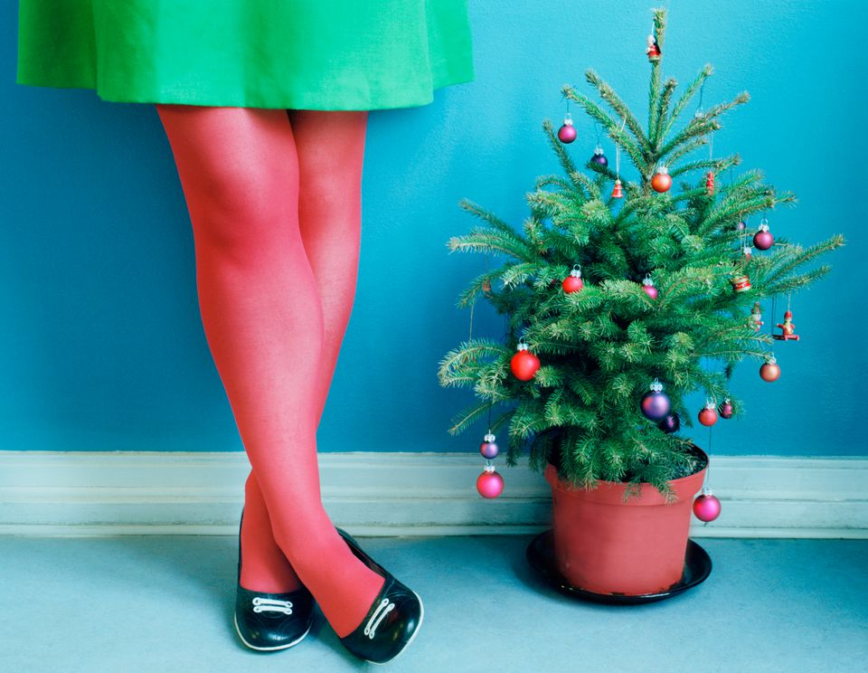 woman in red stockings next to mini Christmas tree
