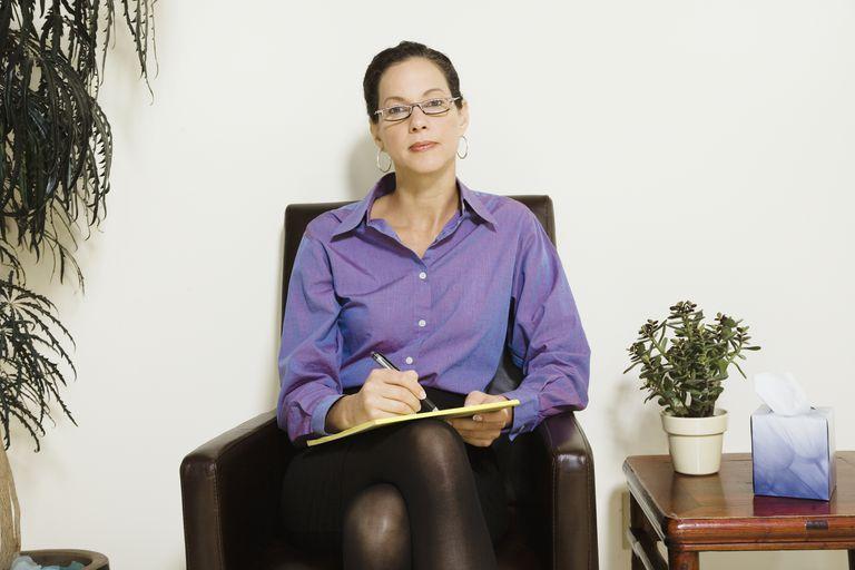 Mixed Race female psychiatrist holding notepad