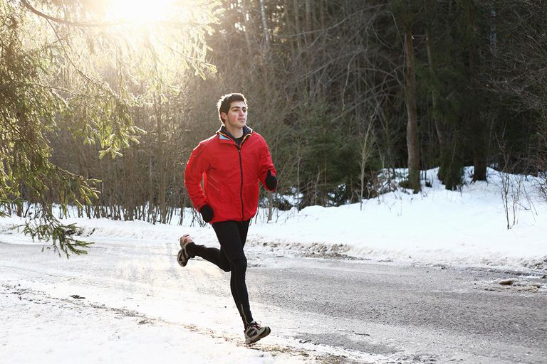 Runner on forest snowy road in the morning