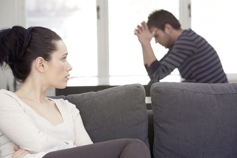 Young woman sitting on sofa, looking at distressed man at table