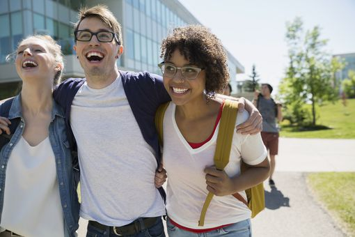 Laughing college students hugging on campus
