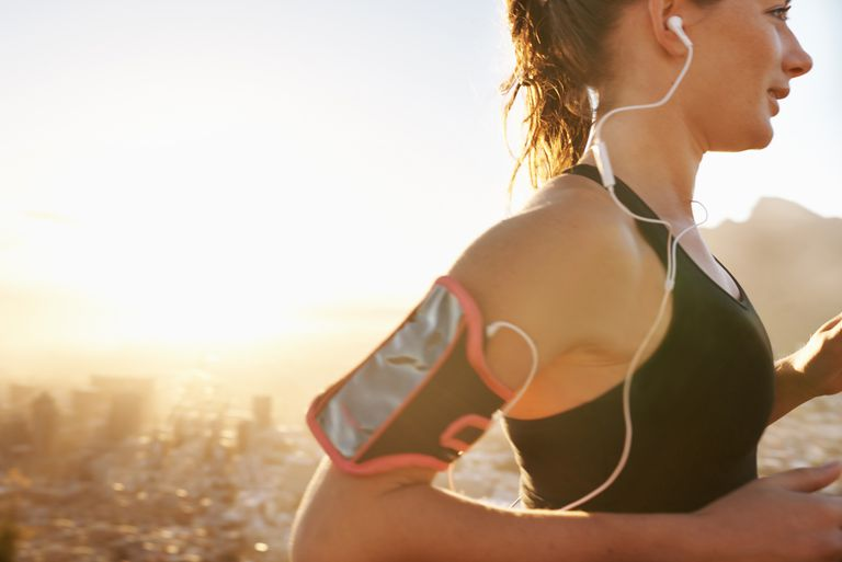 Woman running with headphones and her phone strapped to her arm