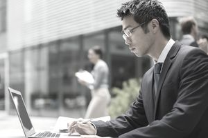 Businessman working on laptop outside of office building