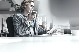 agent talking on her cellphone studying paperwork