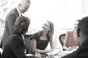 Mature employee leading a discussion with four colleagues