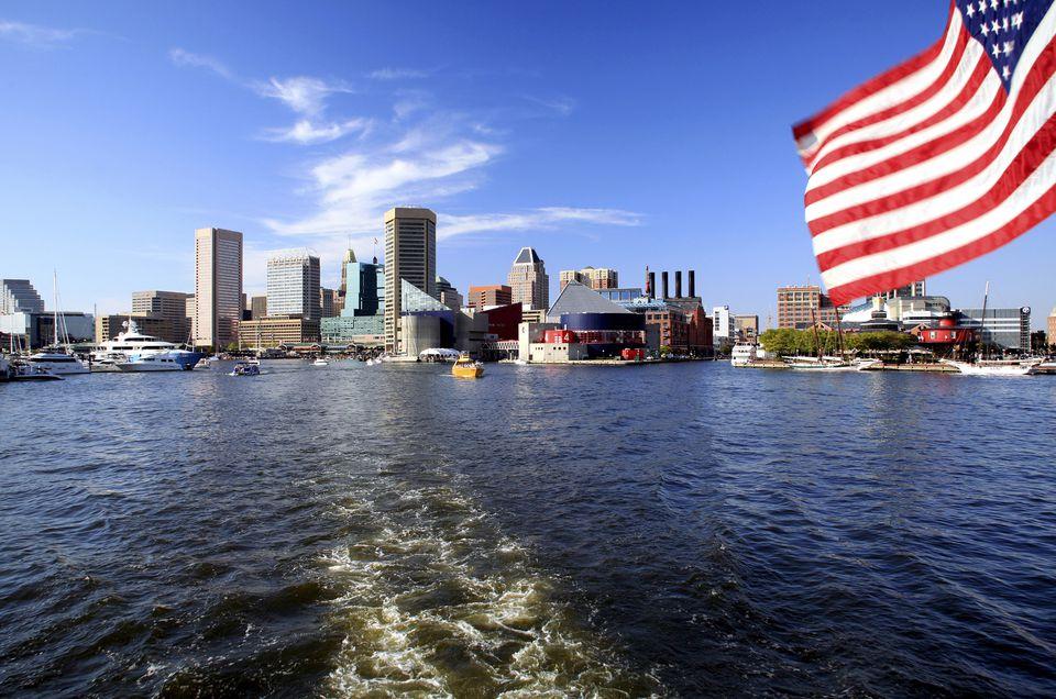American flag flying over Inner Harbor and Baltimore skyline, Baltimore, Maryland, USA