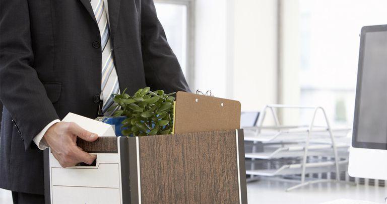 Business man carrying filing box of belongings