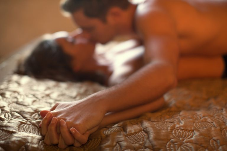 Kissing couple holding hands in bed