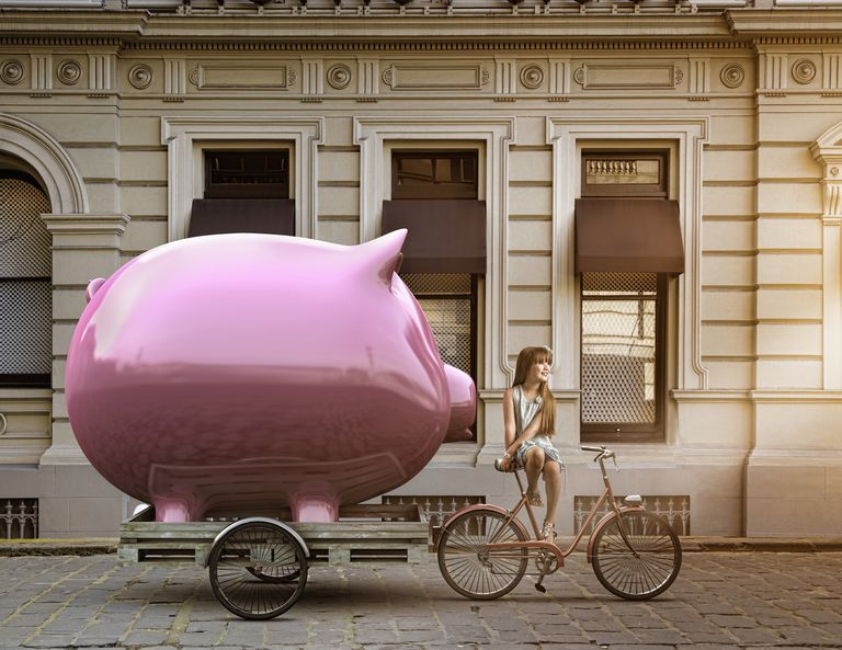 Caucasian girl pulling piggy bank on bicycle cart