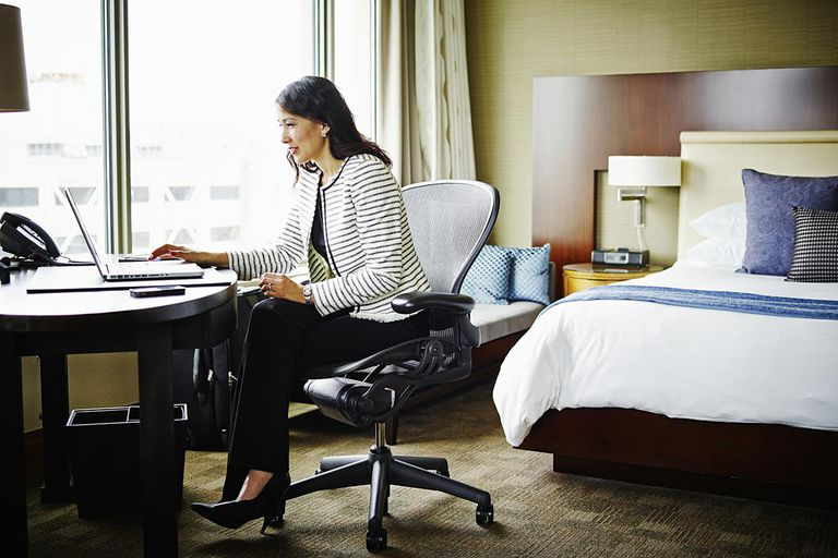Businesswoman sitting at desk in hotel room working on laptop
