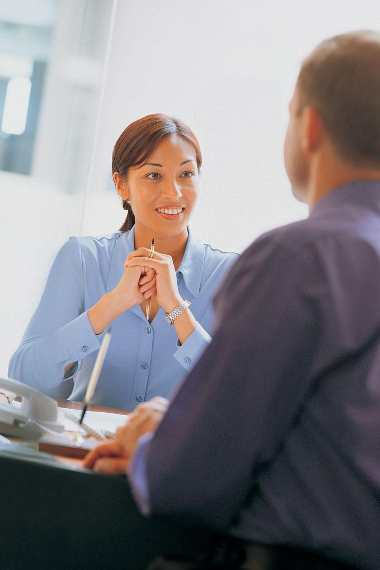 Woman at desk talking with man