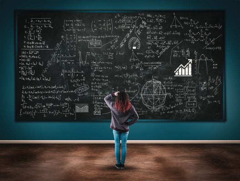 Confused girl in front of a blackboard full of formulas.