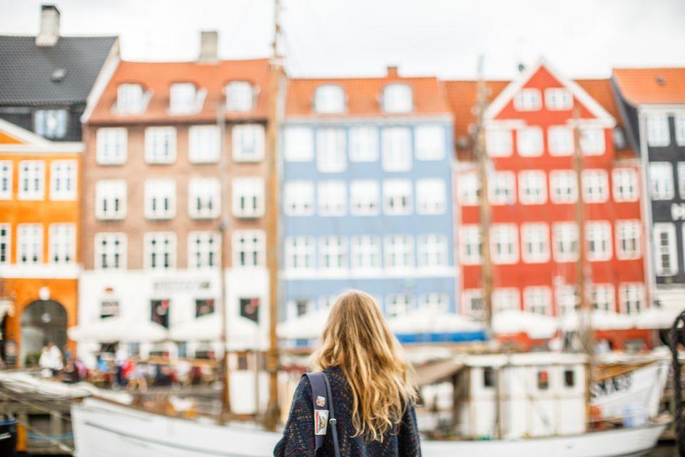 A tourist looks at a view of Nyhavn, Copenhagen, Denmark