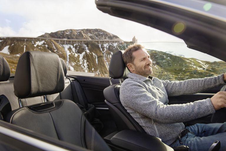 Man enjoying ride in an open roof top car.