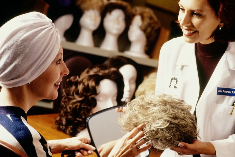 Hospital staff helping chemo patient choose a wig.