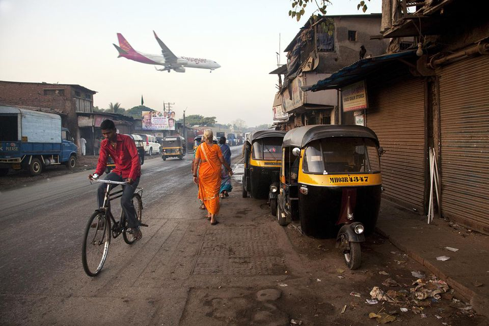 Plane landing at Mumbai International Airport next to slums.