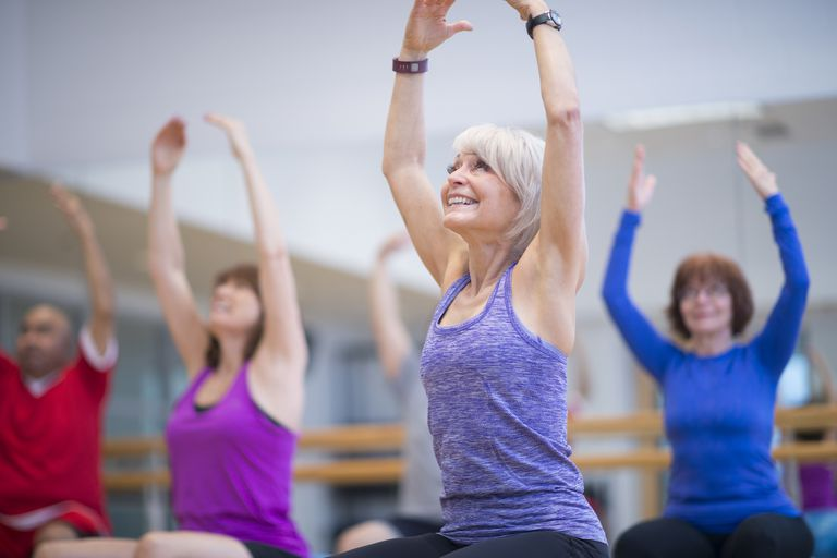 Seniors in a group exercise class sitting on exercise balls and stretching their arms over their heads