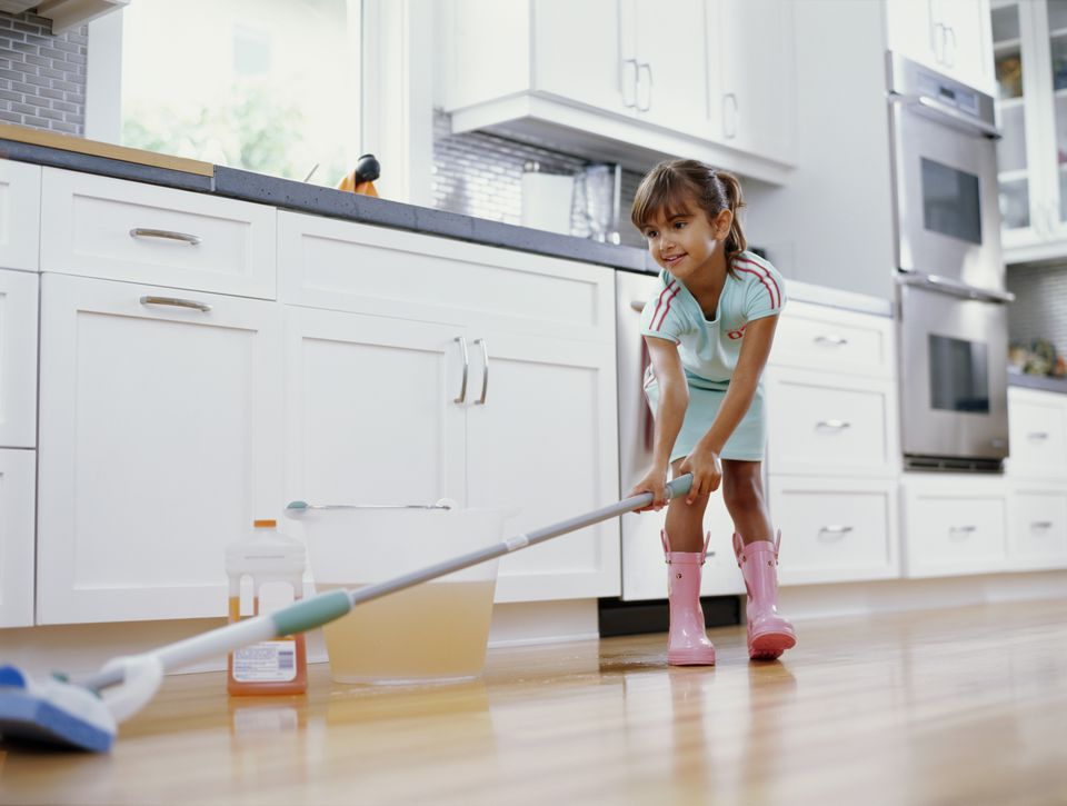 Girl cleaning kitchen floor with mop, smiling, low angle view
