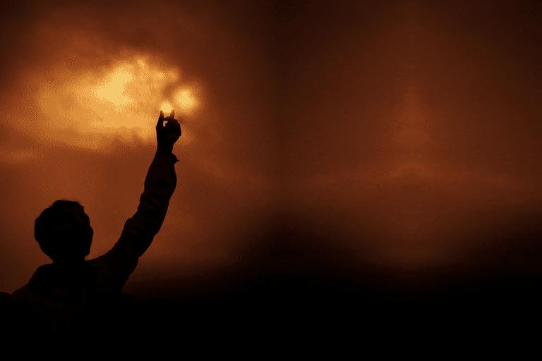 Man reaching toward red cloudy sky