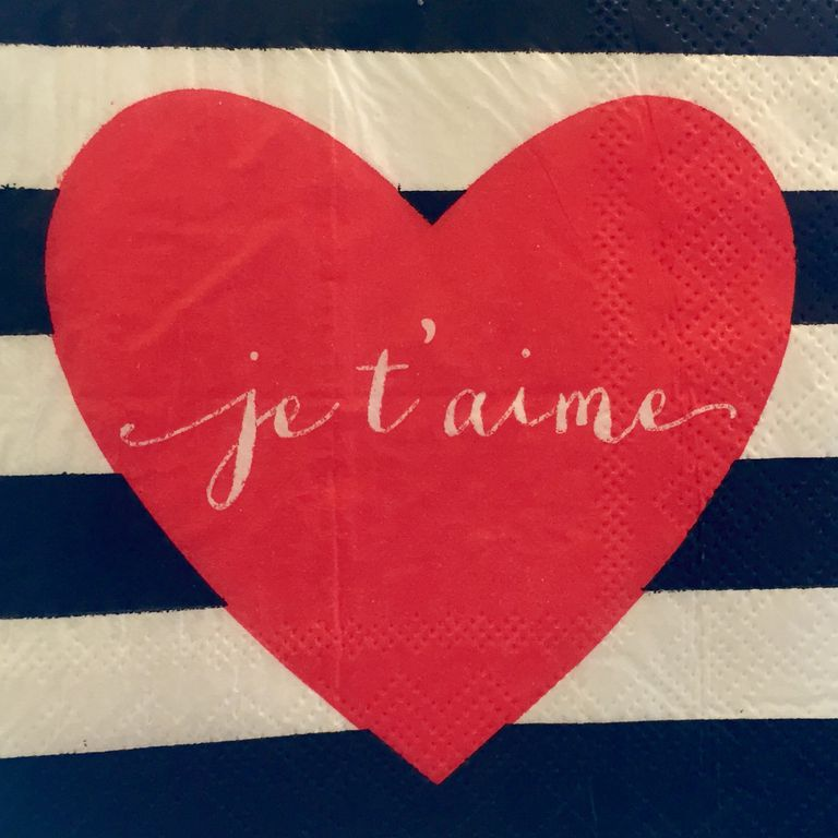 A red heart with 'je t'aime' written inside against blue and white stripes on textured paper
